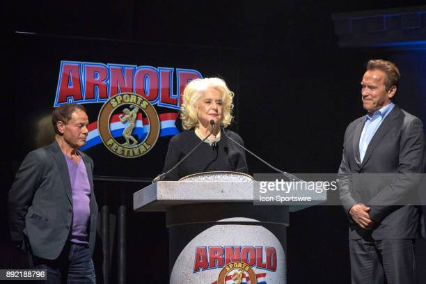 Franco Columbu and Arnold Schwarzenegger look on as Betty Weider addresses the audience after receiving the Lifetime Achievement Award during the...