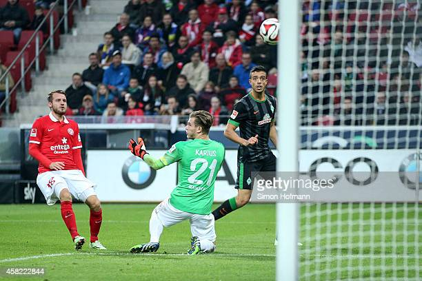 Franco di Santo of Bremen scores his team's second goal against goalkeeper Loris Karius and Daniel Brosinski of Mainz during the Bundesliga match...