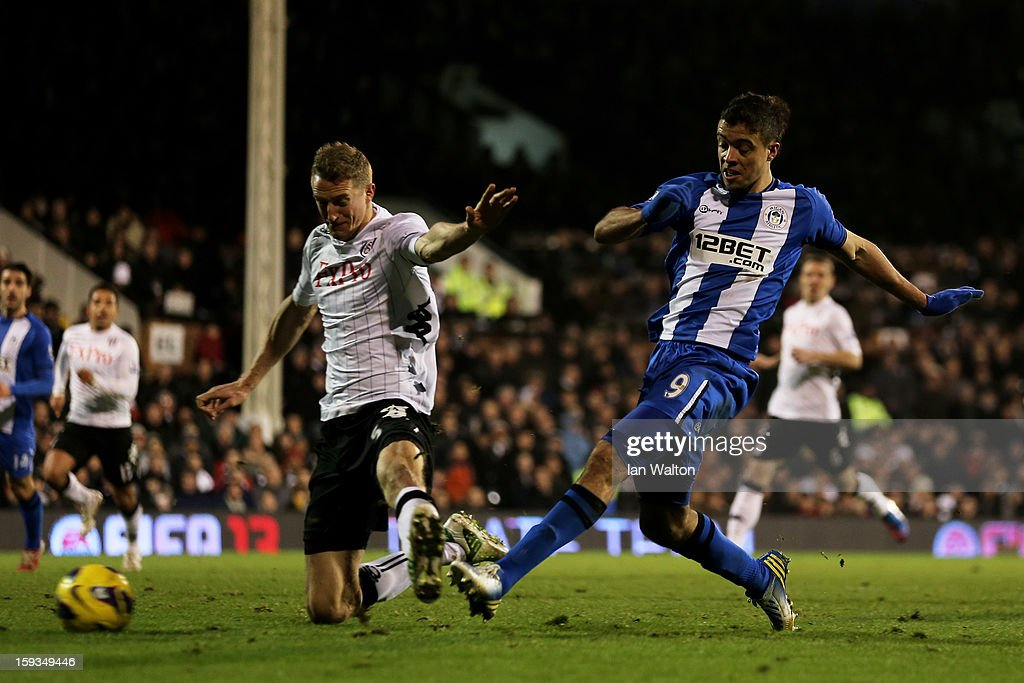 Franco Di Santo of Wigan shoots on goal past the challenge from Brede Hangeland of Fulham during the Barclays Premier League match between Fulham and Wigan Athletic at Craven Cottage on January 12, 2013 in London, England.