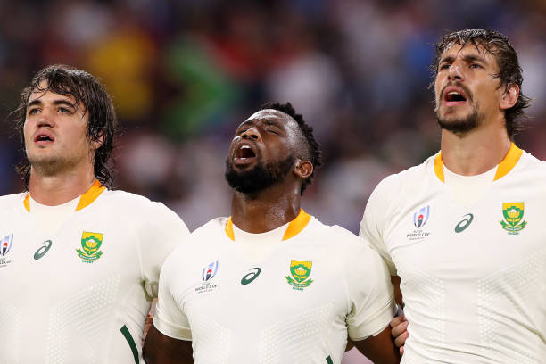 TOYOTA, JAPAN - SEPTEMBER 28: (L-R) Franco Mostert, Siya Kolisi and Eben Etzebeth of South Africa line up for the national anthems prior to the Rugby World Cup 2019 Group B game between South Africa and Namibia at City of Toyota Stadium on September 28, 2019 in Toyota, Aichi, Japan. (Photo by Mark Kolbe/Getty Images)