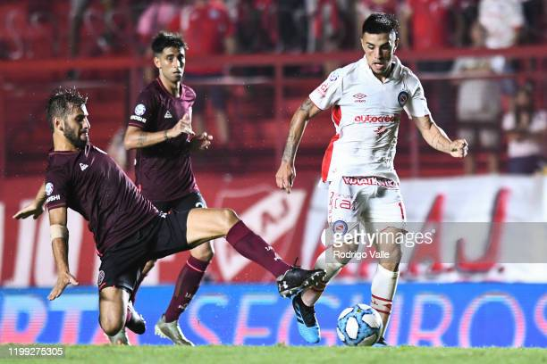 Franco Moyano of Argentinos Juniors fights for the ball with Facundo Quignon of Lanus during a match between Argentinos Juniors and Lanus as part of...