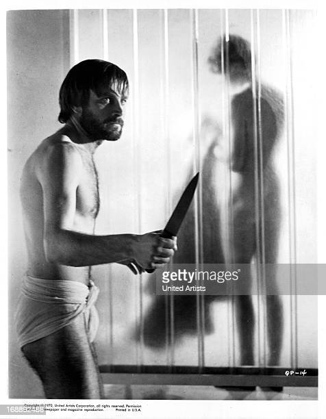 Franco Nero holds a knife while Vanessa Redgrave takes a shower in a scene from the film 'A Quiet Place In The Country' 1968