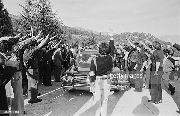 Franco supporters raise their arms to salute the arrival of Chilean General Augusto Pinochet who is in Spain to attend the funeral of General...