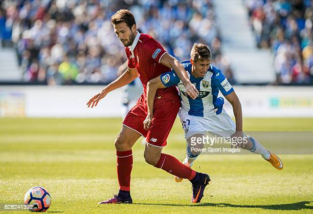 Franco Vazquez of Sevilla FC battles for the ball with Alexander Szymanowski of Deportivo Leganes during their La Liga match between Deportivo...
