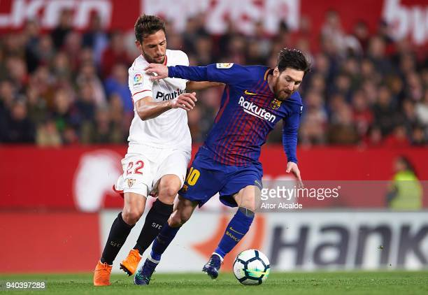 Franco Vazquez of Sevilla FC competes for the ball with Lionel Messi of FC Barcelona during the La Liga match between Sevilla CF and FC Barcelona at...
