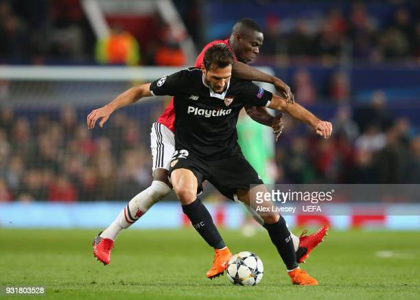 Franco Vazquez of Sevilla FC holds off a challenge from Eric Bailly of Manchester United during the UEFA Champions League Round of 16 Second Leg...