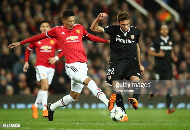 Franco Vazquez of Sevilla is blocked by Chris Smalling of Manchester United during the UEFA Champions League Round of 16 Second Leg match between...