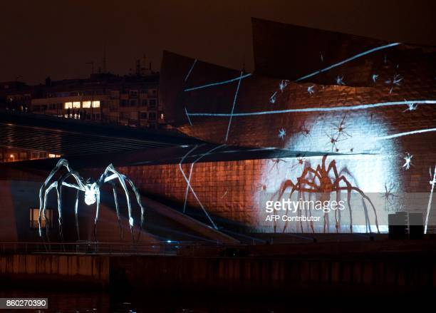 FrancoAmerican sculptor Louise Bourgeois' sculpture 'Maman' projects its shadow against Guggenheim Bilbao Museum during the 'Reflections' mapping...