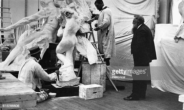 Francois Auguste Rene Rodin [right] French sculptor watches assistants work on plaster casts of his works