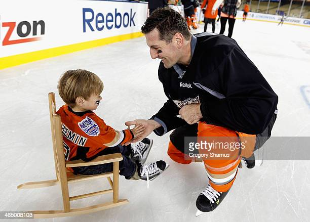 Francois Beauchemin of the Anaheim Ducks skates with his son during the family skate after the team practice for the 2014 Coors Light NHL Stadium...