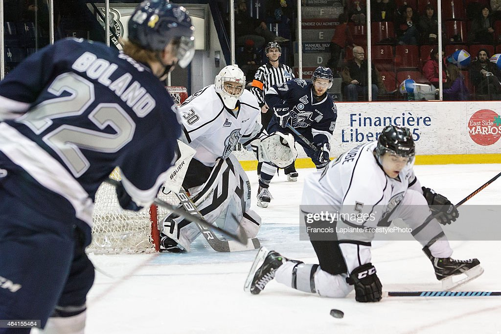 Francois Brassard #30 of the Gatineau Olympiques guards his net as Elie Berube #5 blocks a shot from Tyler Boland #22 of the Rimouski Oceanic on February 22, 2015 at Robert Guertin Arena in Gatineau, Quebec, Canada.