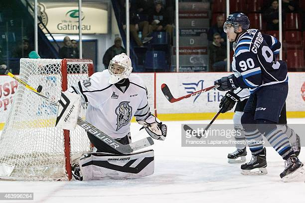 Francois Brassard of the Gatineau Olympiques makes a save as Charles Guevremont of the Chicoutimi Sagueneens keeps position in front of the net...