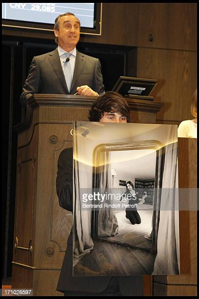 Francois Curiel with behind him a photo of Carla Bruni Sarkozy at Christie's Auction Of Richard Melloul Photographs In Benefit Of Association La...