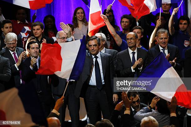 Francois Fillon , candidate for the right-wing primaries ahead of the French 2017 presidential election, waves flanked by Eric Woerth , French member...