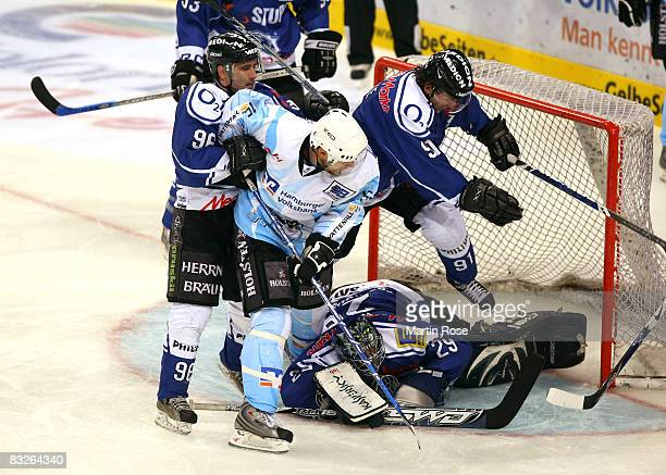 Francois Fortier of Hamburg tries to score over Glen Goodall Jimmy Waite and Rene Roethke of Ingolstadt during the DEL match between Hamburg Freezers...