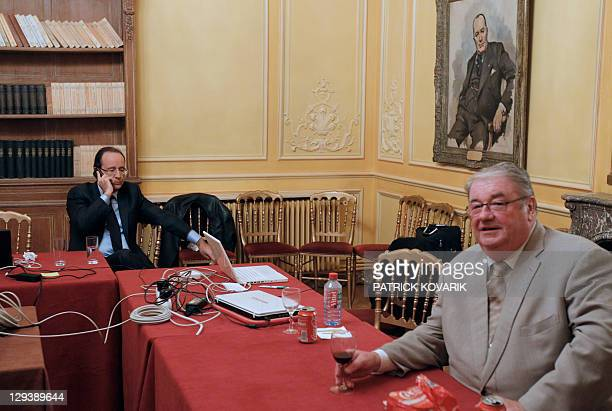 Francois Hollande winner of the Socialist Party 2011 primary vote for France's 2012 presidential election, gives a phone call to former socialist...