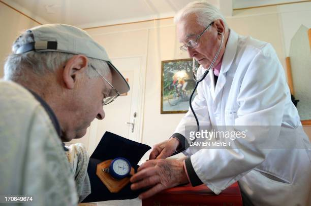 MEYER Francois Le Men a 91 yearold doctor auscultates a patient in his office on June 11 2013 in Callac western France AFP PHOTO/DAMIEN MEYER