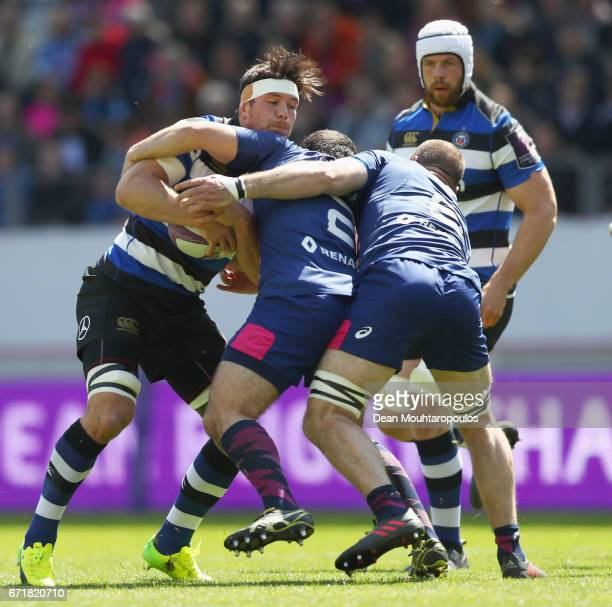 Francois Louw of Bath Rugby is stopped by Laurent Panis and Antoine Burban of Stade Francais during the European Rugby Challenge Cup match between...