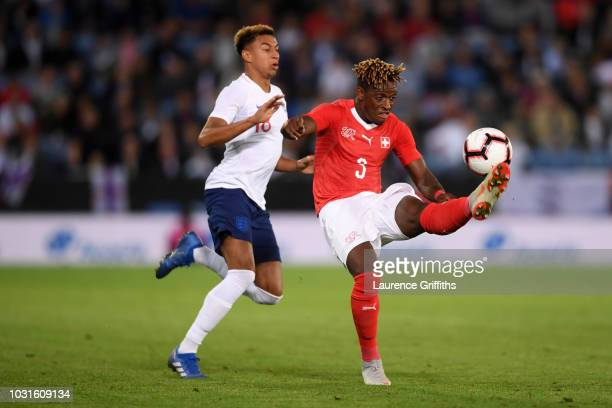 Francois Moubandje of Switzerland clears from Jesse Lingard of England during the international friendly match between England and Switzerland at The...