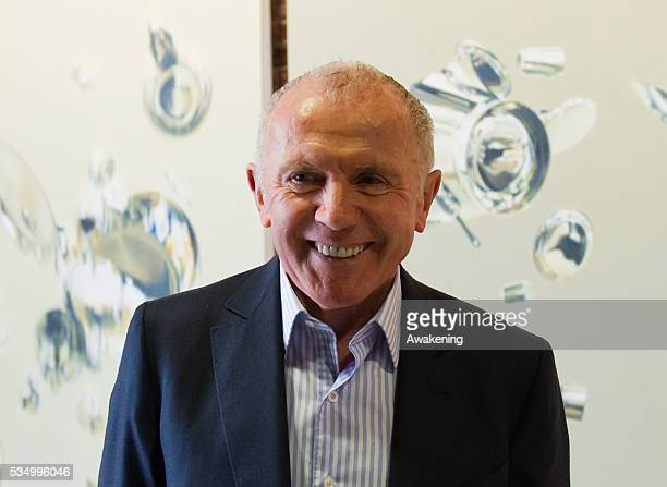 Francois Pinault poses in front of work of Artist Subodh Gupta a t the opening of the Exhibition In Praise of Doubt at Punta della Dogana organised...