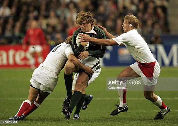 Francois Steyn of South Africa is tackled by England players during the IRB 2007 Rugby World Cup final match between South Africa and England held at...