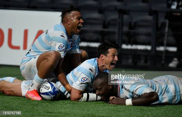 Francois Trinh-Duc of Racing 92 celebrates with teammates Teddy Thomas and Jordan Joseph after touching down for his team's seventh try during the...