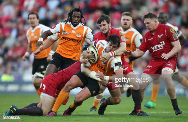 Francois Venter of Cheetahs is held by Hadleigh Parkes of Scarlets and Dan Jones of Scarlets during the Guinness Pro14 match between Scarlets and...