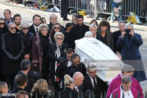 People carry the coffin in the La Madeleine Church at the start of the funeral ceremony in tribute to late French singer Johnny Hallyday on December...