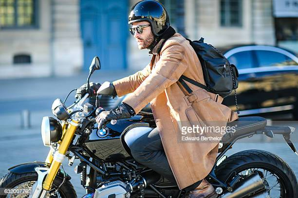 FrancoisXavier Watine photographer from Web Style Story is wearing a Berluti long camel coat sunglasses and is riding a BMW motorbike after the...