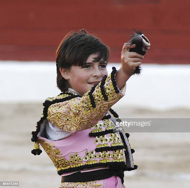 FrancoMexican tenyearold bullfighter Michelito celebrates by holding up part of the bull during a bullfight at the bullring in Merida Yucatan state...