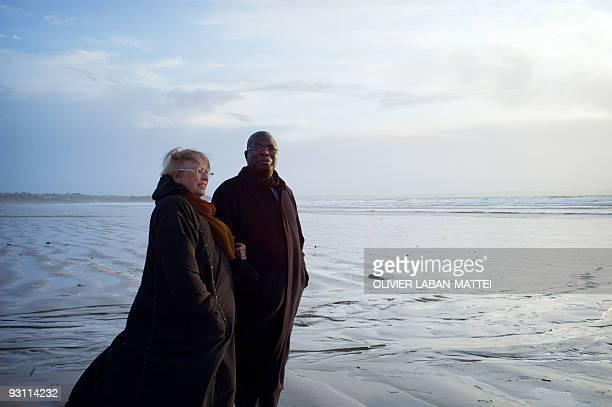 Franco-Togolese dual national politician Kofi Yamgnane walks with his wife Anne-Marie on the beach of Saint-Nic, western France, on November 14,...
