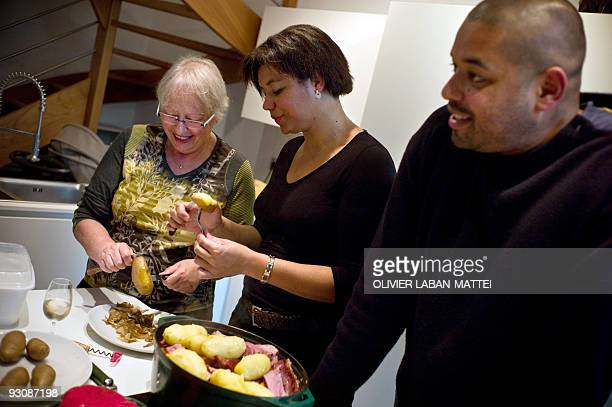 Franco-Togolese dual national politician Kofi Yamgnane's wife Anne-Marie prepares a meal with their daughter Amina at the house of their son Kwame on...