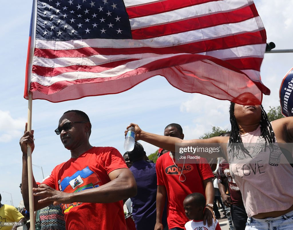 Frandzy Bruce Bernadin (L) joins others as they protest the possibility that the Trump administration may overturn the Temporary Protected Status for Haitians in front of the U.S. Citizenship and Immigration Services office on May 13, 2017 in Miami, Florida. 50,000 Haitians have been eligible for TPS and now the Trump administration has until May 23 to make a decision on extending TPS for Haitians or allowing it to expire on July 22 which would mean possibly deportation for the current TPS holders.