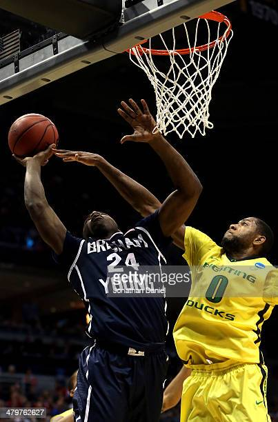 Frank Bartley IV of the Brigham Young Cougars shoots as Mike Moser of the Oregon Ducks defends during the second round game of NCAA Basketball...