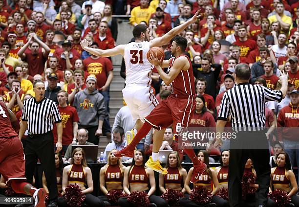 Frank Booker of the Oklahoma Sooners is fouled by Georges Niang of the Iowa State Cyclones as he takes a three point shot in the second half of play...
