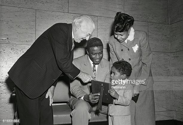 Frank C Gannett publisher of Gannett Newspapers leans over to shake hands with Jackie Robinson second baseman for the Brooklyn Dodgers who was...