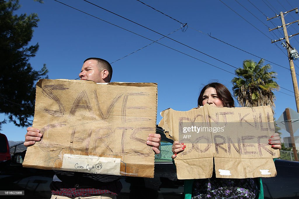 Frank Cardiel (L) and Shantel Cardiel hold up signs in support of fugitive triple murder suspect Christopher Dorner along the road in San Bernardino, California n February 12, 2013. Fugitive former US cop Christopher Dorner exchanged gunfire with police near a Californian ski resort where his burnt-out truck was found, reports said. The 33-year-old was involved in the shooting after he tried to burglarize a home near Big Bear, two hours east of Los Angeles, the Los Angeles Times reported, citing a law enforcement source.  AFP PHOTO / David McNew