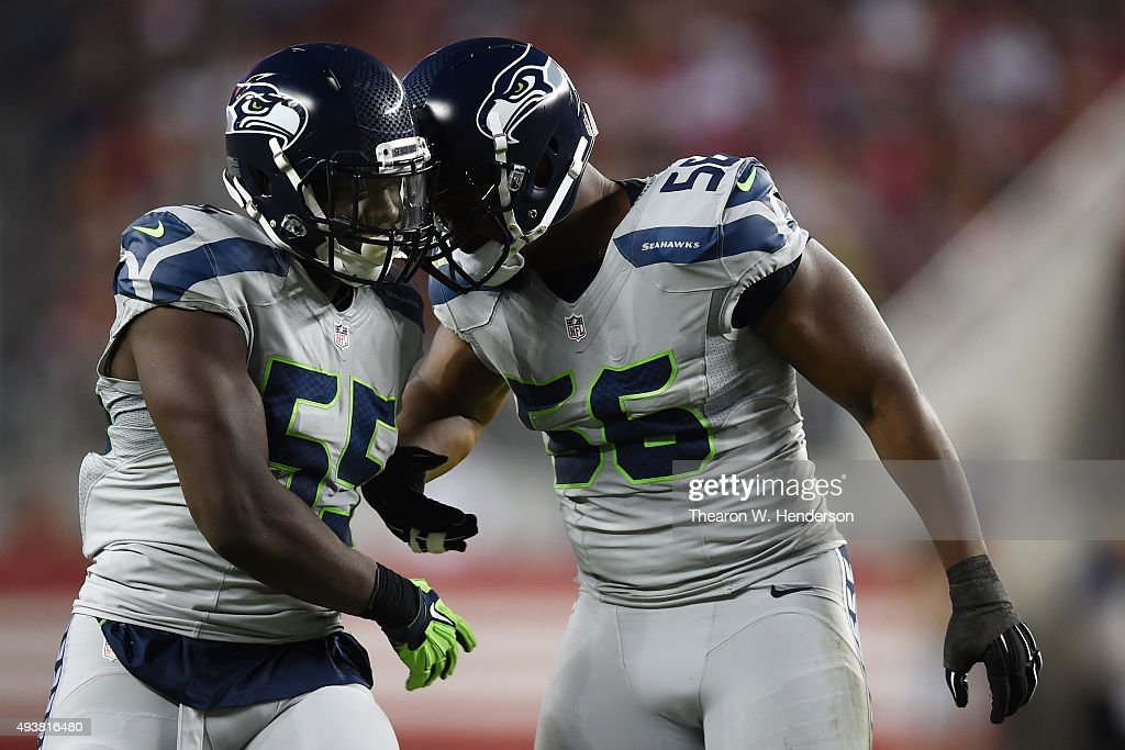 Frank Clark #55 and Cliff Avril #56 of the Seattle Seahawks react after a sack on Colin Kaepernick #7 of the San Francisco 49ers during their NFL game at Levi's Stadium on October 22, 2015 in Santa Clara, California.