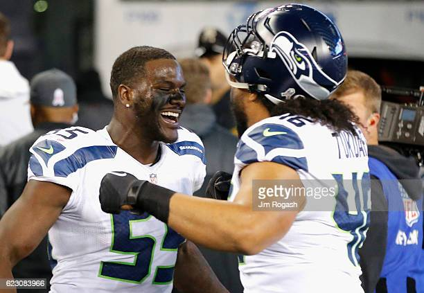 Frank Clark and Will Tukuafu of the Seattle Seahawks react following a game against the New England Patriots during a game at Gillette Stadium on...