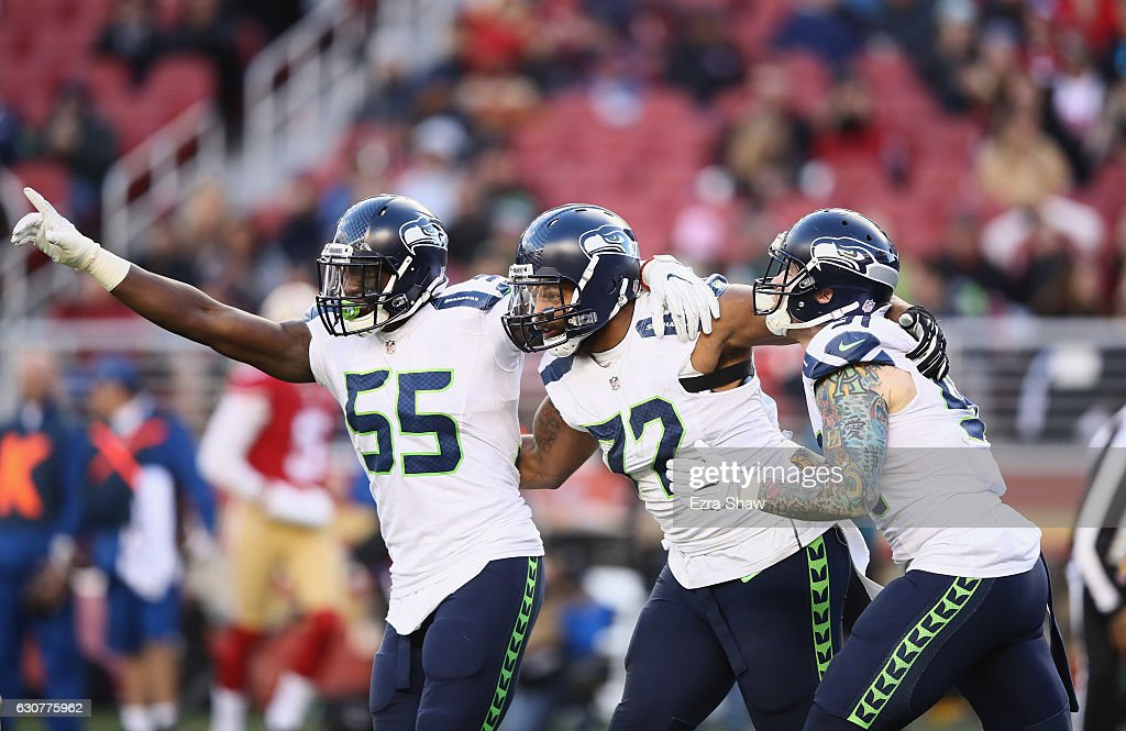 Frank Clark #55, Michael Bennett #72, and Cassius Marsh #91 of the Seattle Seahawks react after Bennett tackled Colin Kaepernick #7 of the San Francisco 49ers at Levi's Stadium on January 1, 2017 in Santa Clara, California.