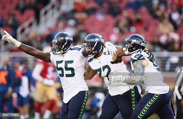 Frank Clark Michael Bennett and Cassius Marsh of the Seattle Seahawks react after Bennett tackled Colin Kaepernick of the San Francisco 49ers at...