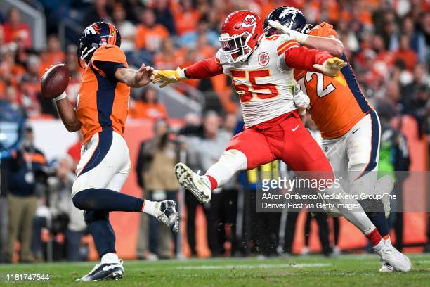 Frank Clark of the Kansas City Chiefs is held by Garett Bolles of the Denver Broncos before forcing a fumble on Joe Flacco during the third quarter...