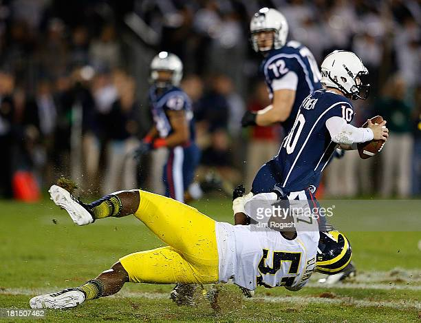Frank Clark of the Michigan Wolverines gets a piece of Chandler Whitmer of the Connecticut Huskies in the 4th quarter against the Connecticut Huskies...