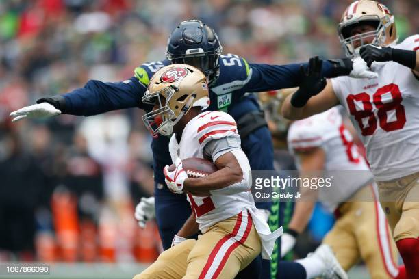 Frank Clark of the Seattle Seahawks attempts to tacks Matt Breida of the San Francisco 49ers in the first quarter at CenturyLink Field on December 2...