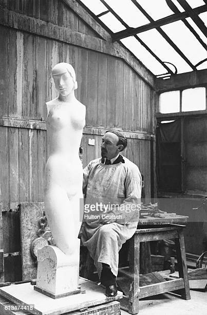 Frank Dobson at work on a sculptured mannequin of the ideal female figure for the 20th century to be used in a corset display The sculpture is based...