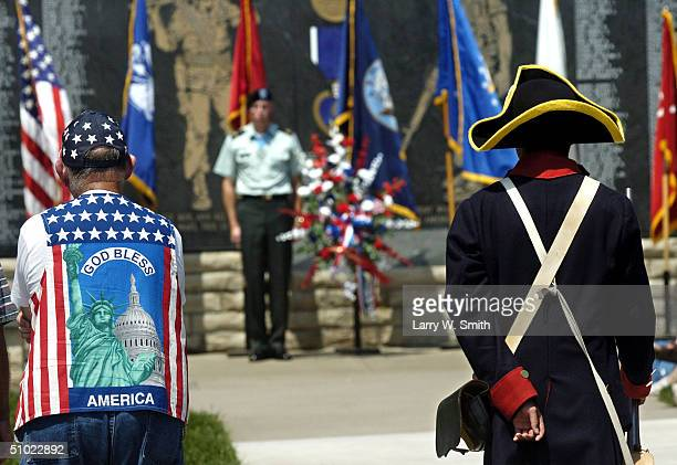 Frank Drew of Junction City Kansas and Private First Class Kim Sun listen to a speech while Staff Sergent Gary Moore stands next to a ceremonial...