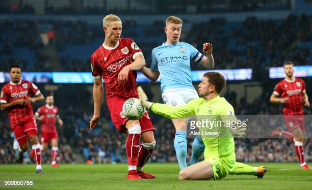Frank Fielding and Horour Magnusson of Bristol City foil Kevin De Bruyne of Manchester City during the Carabao Cup SemiFinal First Leg match between...