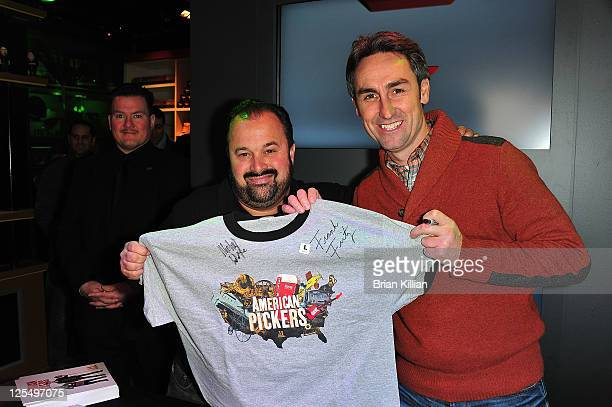 Frank Fritz and Mike Wolfe from American Pickers autograph a tshirt for a fan during the grand opening of the History Pop Shop at History Pop Shop on...