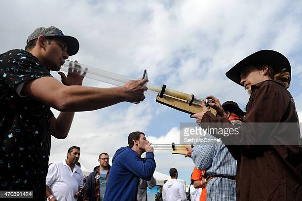 Frank Froman takes a hit from the I420 Double Barrel Shotgun pipe by Incredibowl being held by Rolf Johnson during the High Times Cannabis Cup at the...