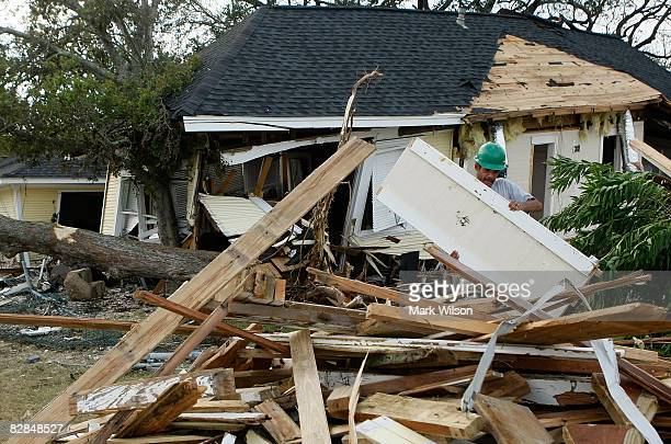 Frank Garcia helps clean debris from a home demolished by Hurricane Ike September 16 2008 in Kemah Texas Hurricane Ike caused widespread damage and...